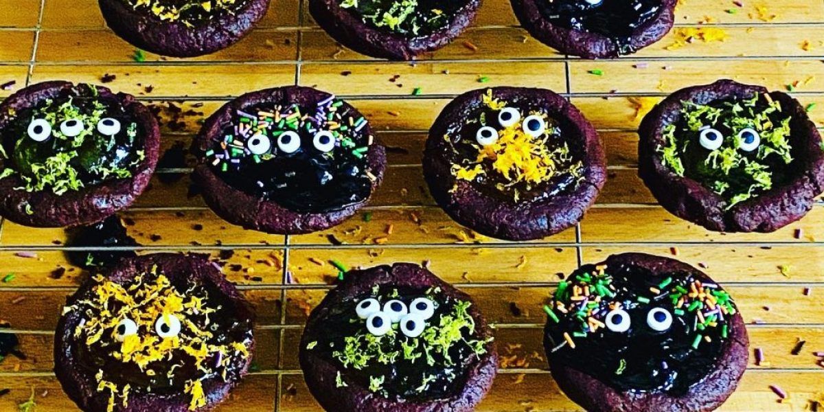 Monster cookie cups filled with jam and marmalades, topped with icing eyes, sprinkles and orange and lime zest