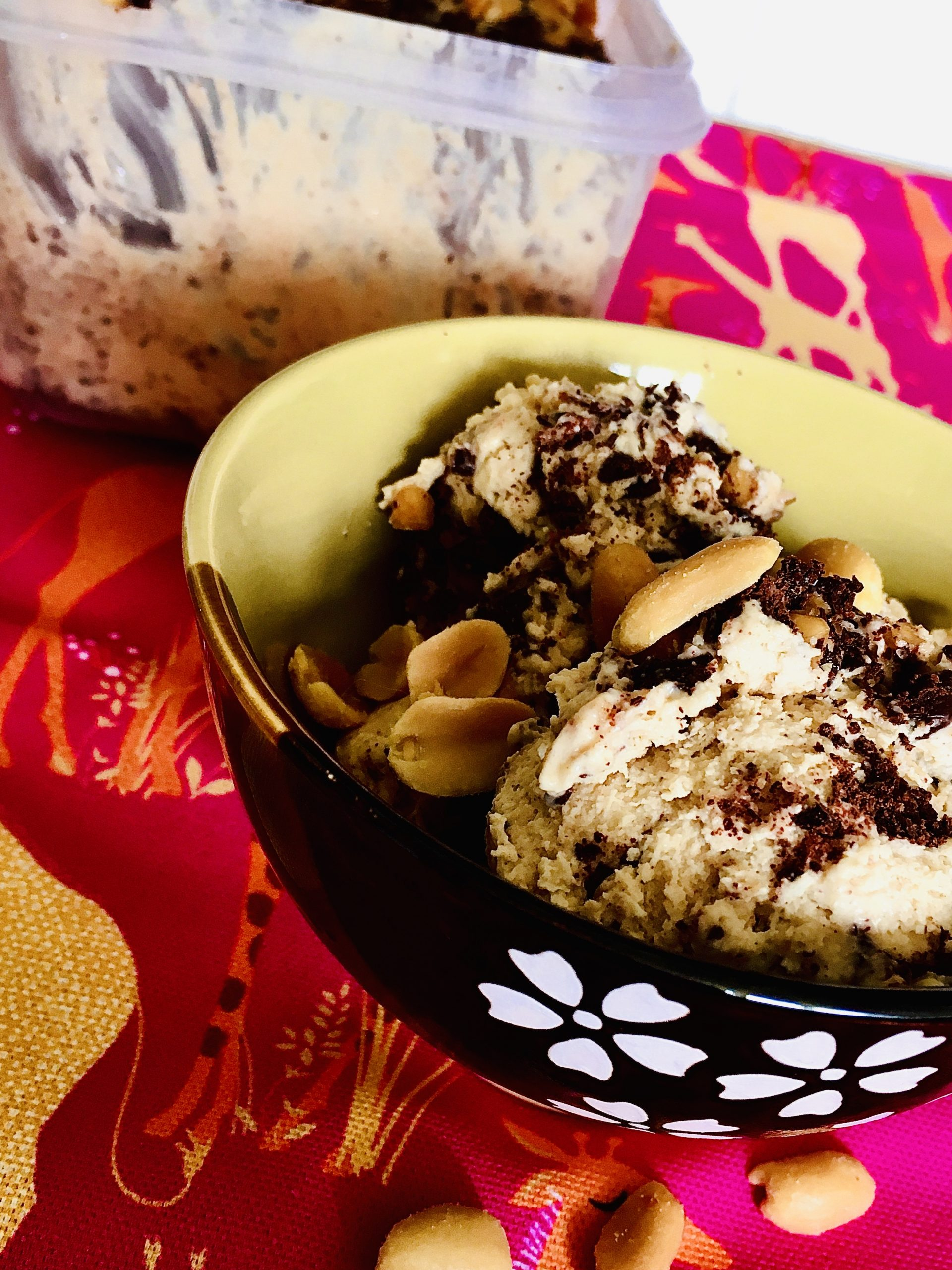Scoops of peanut butter and chocolate swirl ice cream in a bowl on a pink cloth, next to the ice cream tub