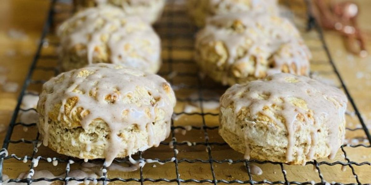 6 maple chai scones drizzled with icing on a wire rack on a wooden table