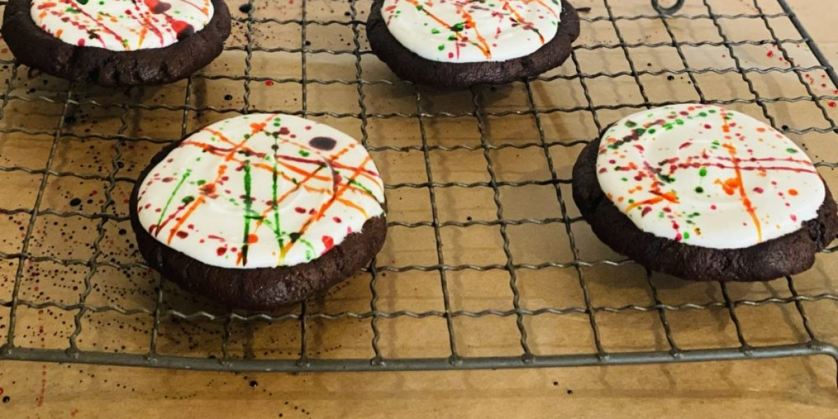 Halloween splatter cookies on a wire baking rack decorated with purple, green and orange colouring