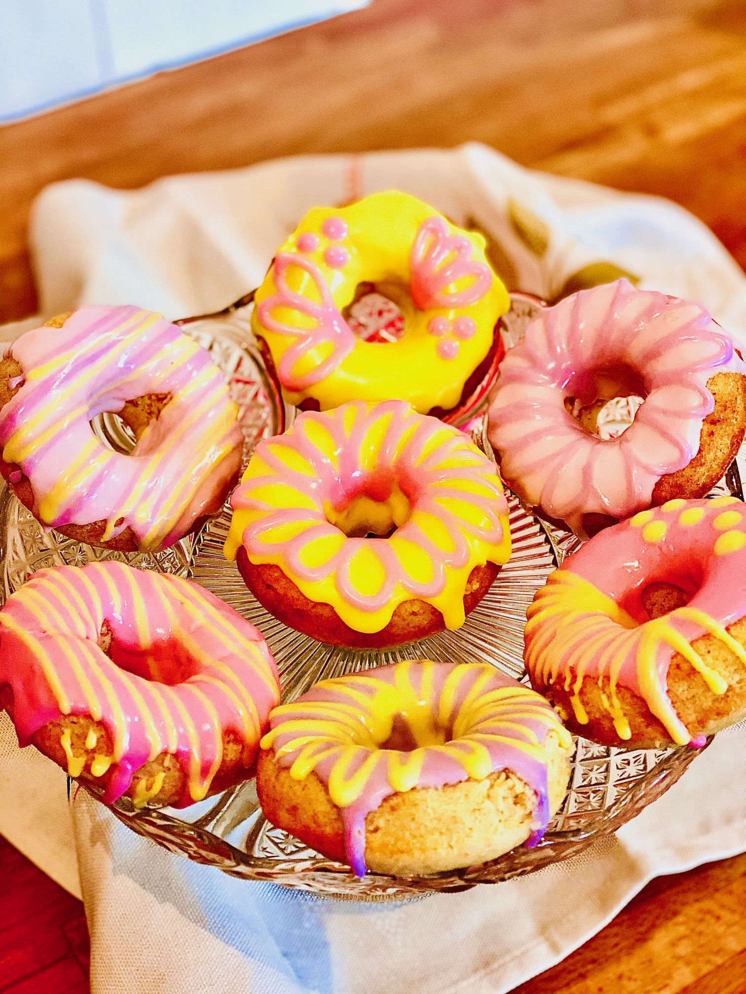 Baked doughnuts topped with coloured icing displayed on a cake stand