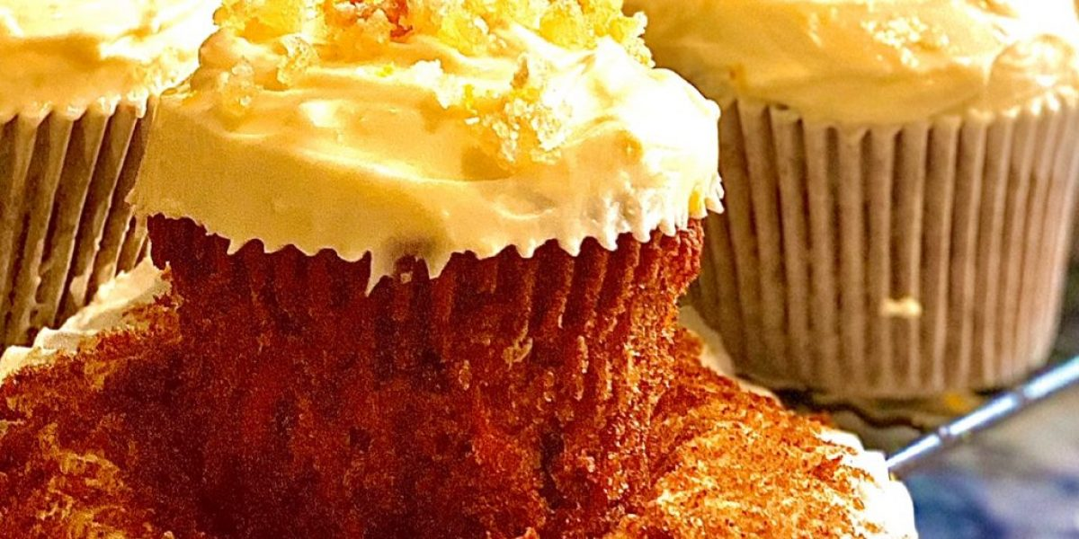 Lemon and ginger carrot cake cupcakes on a baking wrack. The front cake as the cake case turned down to show the carrot cake below contrasted with the pale cream cheese frosting.