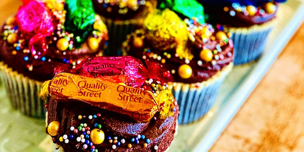 6 chocolate and dulce de leche cupcakes with chocolate icing and topped with a variety of Quality Street chocolates and gold sprinkles