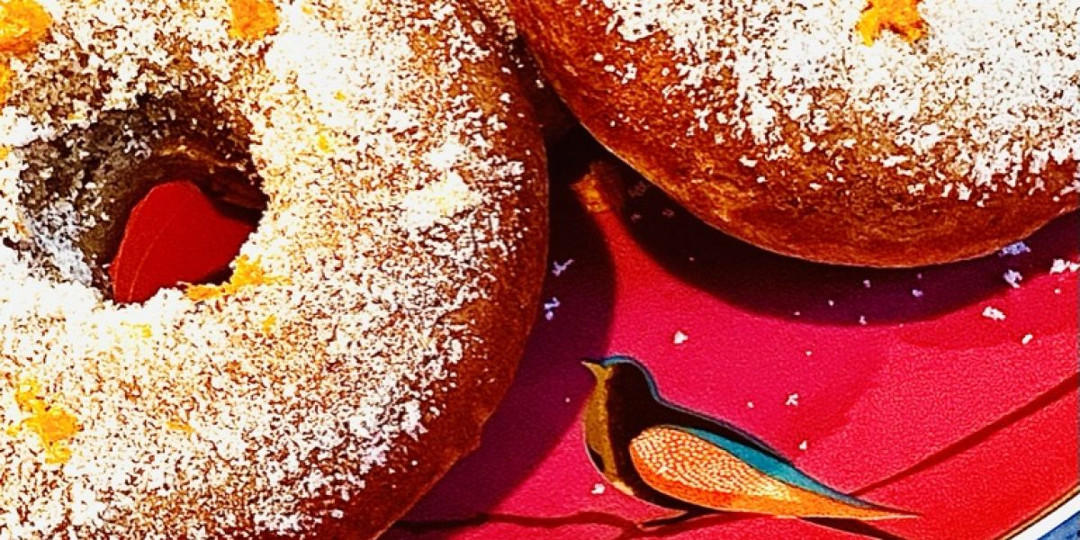 Baked banana and cinnamon breakfast doughnuts with orange sugar. Displayed on a plate with orange slices below for decoration.