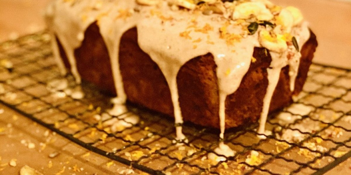 Chai banana bread on a cooling rack decorated with maple and orange icing and decorated with banana chips and seeds with orange zest
